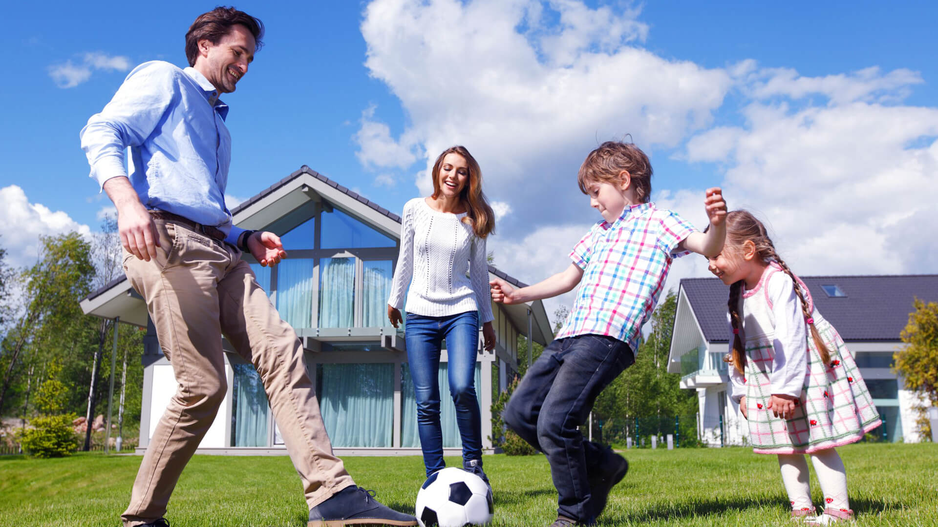 family kicking soccer ball on lawn