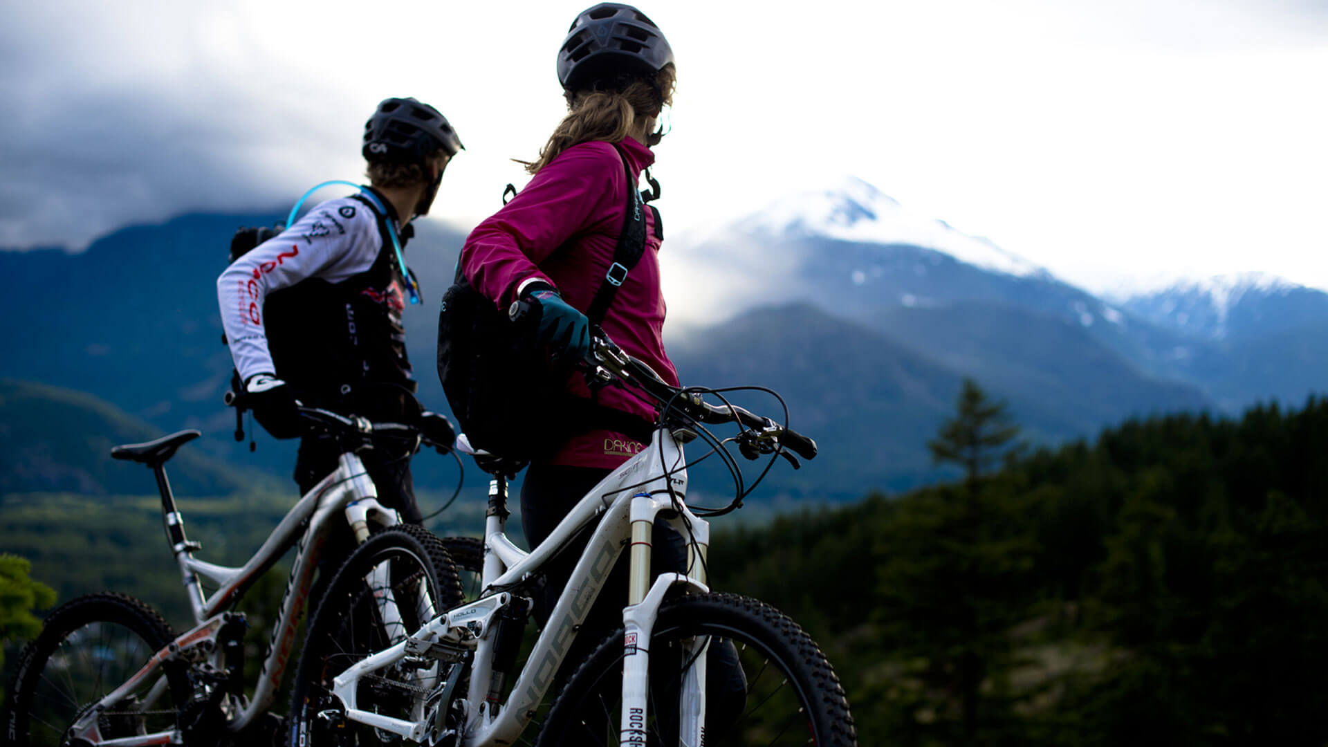 young male and female dressed in biking gear looking at mountain